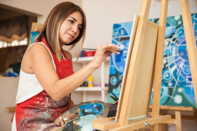 A young, female college student painting in a studio.